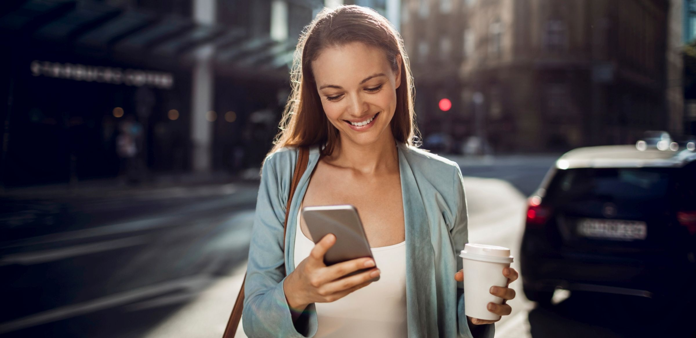 Woman typing on her mobile phone, smiling and holding coffee